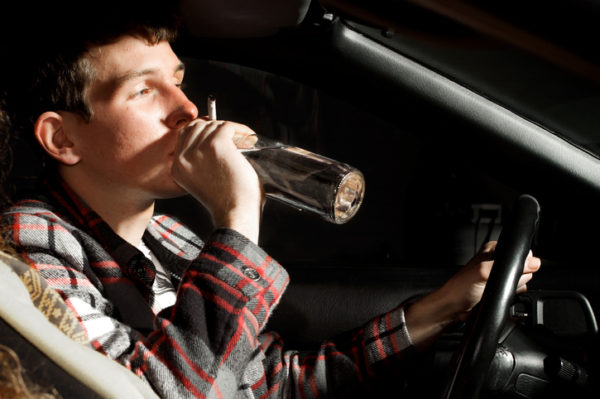A young man drinking alcohol while driving